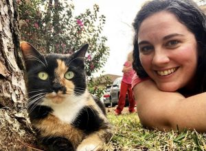 Ground level selfie of a calico cat and a woman lying next to her, smiling