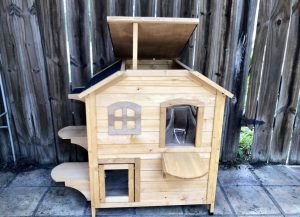 Cedar cat house with two floors, several openings and ledges, and a propped up roof