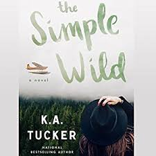 A book cover with a photo image of a person facing away from the camera, hand holding her hat onto her head, looking out at a forest of trees and a plane in the sky. The title, The Simple Wild, is written in brushstroke font in the sky. The author is K. A. Tucker.