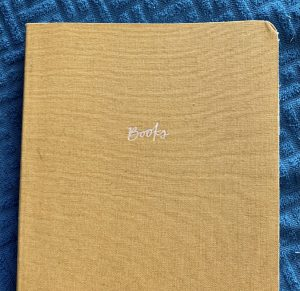 A yellow notebook on a blue textured background. The notebook says Books on the cover.