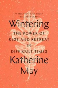 "A red-orange book cover with the title, ""Wintering: The Power of Rest and Retreat in Difficult Times,"" and the author's name, Katherine May, printed in black over a pale, cream-colored leaf."