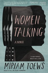 "A blue book cover with the repeated image of a Mennonite woman's head and shoulders in profile. In the black space of her silhouette, the title, Women Talking, is printed, along with with the words ""a novel,"" ""a national bestseller,"" and the author's name, Miriam Toews."