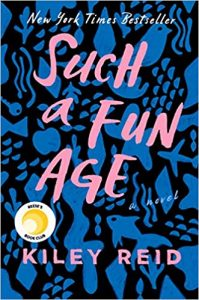 An abstract blue and black book cover with silhouettes of a bird, key, plane, fish, and leaves. The title is in pink across the majority of the book -- Such a Fun Age -- and the author, Kiley Reid, is listed at the bottom.