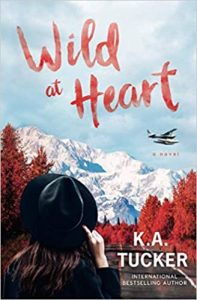 A photorealistic book cover with a woman facing away from the camera, looking at an empty road, fiery red trees in the process of changing colors, and a snowy mountain in the distance. A plan flies in the sky, and she's holding onto her black hat with one hand. The title is in red brushstroke font in the sky: Wild at Heart. The author's name appears over the road: K.A. Tucker.